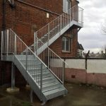 External steel fire escape staircase with vertical infill bar balustrasde and closed riser checker plate treads