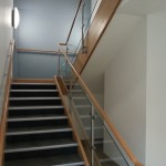 Stainless steel balustrade with timber top rail and 10mm toughened glass infill panels