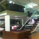 Mezzanine floor with staircase and frameless glass balustrade at Birmingham Airport