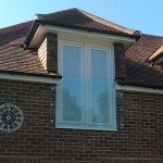 Prefixed juliette balcony shaped around guttering, held in place with 6 nr stainless steel glass adaptors