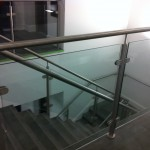 Stainless steel balustrade with glass infill panels and wall rail