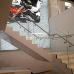 Steel staircase with terrazo flooring and frameless glass balustrade