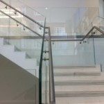 Steel staircase finished in terrazzo with frameless glass balustrade