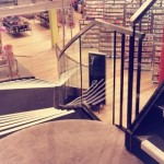 Curved staircase with frameless glass balustrade at Paperchase Glasgow