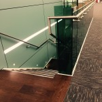 Steel staircase at MTC with frameless glass balustrade and timber treads and landings