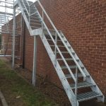 Steel fire escape stairs with open grille treads, galvanised finish
