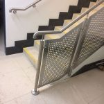 Stainless steel balustrade with perforated infill panels and matching wall rail to staircase
