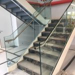 Internal feature staircase under construction, with double stringers, full risers, concrete filled tray treads, frameless glass balustrade and stainless steel rails