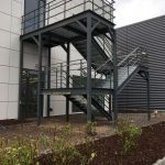 External steel staircase, powder coated RAL 7012 with top+mid rail balustrade, stainless steel handrail and Elefant grating treads