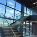 Steel staircase with powder coated double stringers, frameless glass balustrade, stainless steel slotted channel tube top rail