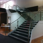 Stainless steel balustrade with glass infill panels up staircase