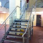 Steel staircase with stainless steel balustrade with glass infill panels to both sides