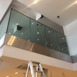 Frameless glass balustrade with toughened laminated glass and 60mm dia stainless steel slotted channel tube top rail plus stainless steel fascia