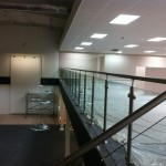 Stainless steel balustrade with glass infill panels up stairs and across gallery