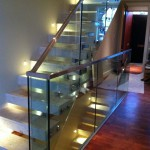 Frameless glazing balustrade up stairs with stainless steel capping