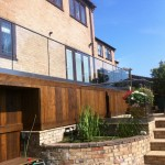 Base fixed aluminium U-channel with 15mm toughened glass and stainless steel slotted tube top rail