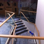 Frameless glass balustrade with timber top rail in a retail unit