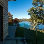 Frameless glass balustrade with no top rail overlooking beautiful view of lake