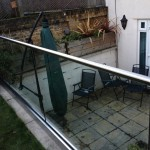 Frameless glass balustrade with top rail based fixed to garden wall