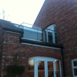 Frameless glass balustrade with 15mm toughened glass resin fixed into channel and stainless steel slotted tube top rail fixed back to wall