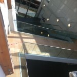 Frameless glass balustrade with stainless steel slotted tube top rail to walkway