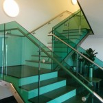 Feature staircase at MTC with green tinted frameless glass balustrade