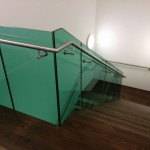 Feature staircase at MTC with green tinted frameless glass balustrade and oak treads