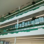 Frameless glass balustrade to atrium area with stainless steel handrail and green tinted toughened laminated glass