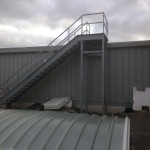 Steel fire escape staircase to roof with a galvanised finish and running rails balustrade