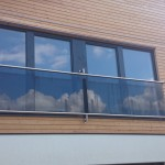 Wall flanged juliette balcony with slotted tube top and bottom rails, tinted glass infills, supported top and bottom
