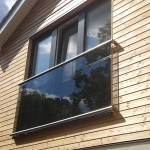 Wall flanged juliette balcony with stainless steel slotted channel tube top and bottom and tinted glass infill panels