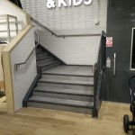 Powder coated mild steel vertical infill bar balustrade with stainless steel top rail to customer staircase