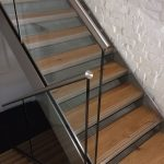 Steel staircase with stainless steel cladding to stringers, frameless glass balustrade, stainless steel slotted channel tube top rail
