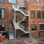 Galvanised steel fire escape staircase with checker plate treads and vertical infill bar balustrade