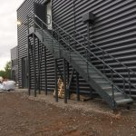External steel staircase, powder coated RAL 7012 with top+mid rail balustrade and Elefant grating treads