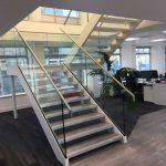 Steel staircase with double stringers, frameless glass balustrade, stainless steel handrail