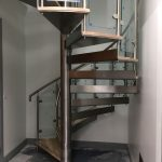 Spiral staircase with stainless steel centre pole, tread plates and balustrade plus curved glass infill panels