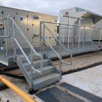 Galvanised steel walkway with handrail standards and open grille flooring
