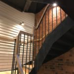Steel staircase with vertical infill bar balustrade, timber top rail and treads