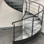 Spiral staircase with galvanised central pole and treads, plus black horizontal running rail balustrade