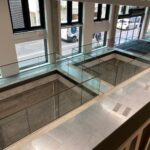 Frameless glass balustrade with bronze ppc capping